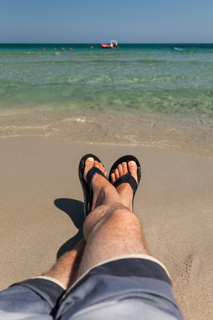 Mens Legs Relaxing on a sandy tropical beach with shorts and flip flops