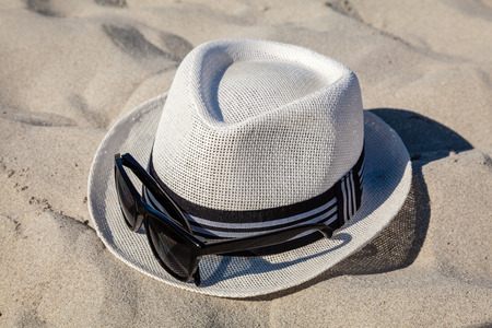 White straw fedora hat on sandy beach with black rimmed polarized sunglasses