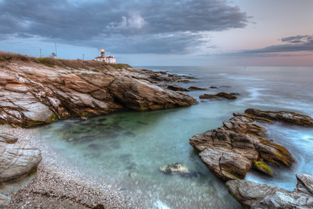 state park: This is a long exposure HDR photo of Beavertail Lighthouse at sunset near Jamestown in Rhode Island, USA  This is a rocky coastal travel seascape  Stock Photo
