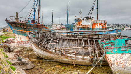 fishing fleet: Camaret sur Mers aged fishing fleet sits at the pier only to move with the tide. Stock Photo