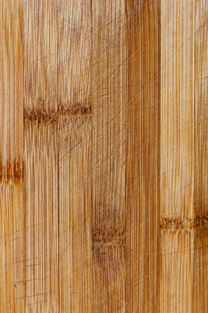 table surface: This is a vertical image of a brown, bamboo, wooden cutting board  The image can be used as a background or a texture or for food and cooking accessory image