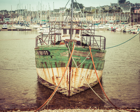mooring: Old abandoned vintage fishing boat moored on the beach in France. Stock Photo