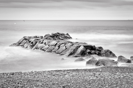 fine art: Fine art black and white image of a rocky jetty pier, abandoned in the morning smooth sea waves.