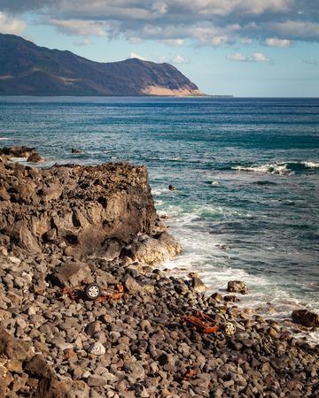 Wreckage of a car along the seascape coastal trail of Kaena Point National Park on Oahu, Hawaii.