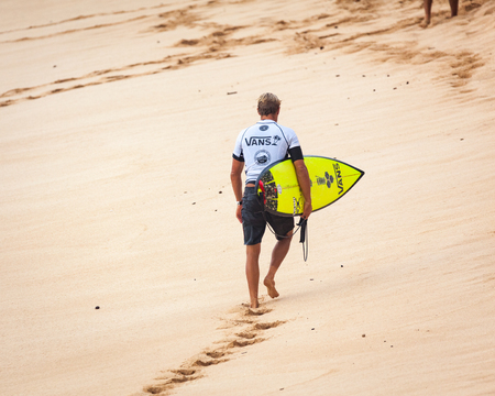 SUNSET BEACH, HAWAII, USA - DECEMBER 2: Competitive surfer walking on beach at the 2017 Vans World Cup of Surfing competition at Sunset Beach on Oahus scenic North Shore. This is the second of three surfing competitions and Conner Coffin took first place