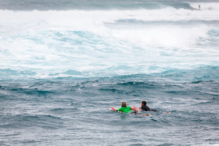 SUNSET BEACH, HAWAII, USA - DECEMBER 2: Surfers paddling out to the break at the 2017 Vans World Cup of Surfing competition at Sunset Beach on Oahus scenic North Shore. This is the second of three surfing competitions and Conner Coffin took first place.