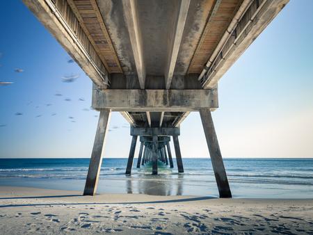 화창한 오후에 포트 월튼 비치, 플로리다에서 Okaloosa 낚시 부두. 비행 중 새들의 움직임을 흐릿하게합니다.