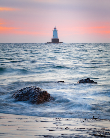Sakonnet Point lighthouse golden hour sunset seascape with smooth silky water and rocky foreground.