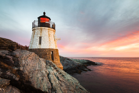 Small Castle Hill Lighthouse sits on the rocky coastline of Newport, Rhode Island at sunset with the waves slowly rushing across the rocks. Imagens
