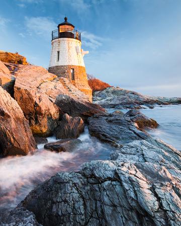 Le petit phare de Castle Hill se trouve sur la côte rocheuse de Newport, Rhode Island au coucher du soleil avec les vagues se précipitant lentement sur les rochers. Banque d'images
