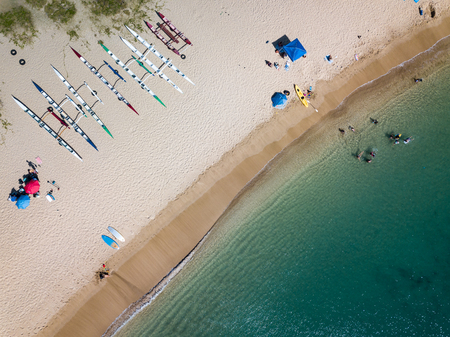 People seen from above, enjoying the tropical beach lifestyle and having fun on the landscape of the island of Oahu, Hawaii, USA.