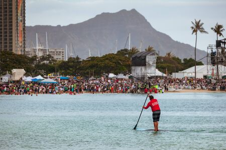 HONOLULU, HAWAII/USA – MAY 28, 2018: Event security on paddle board at lantern floating ceremony at Ala Moana Beach Park on Magic Island in downtown Honolulu, Oahu, Hawaii, USA. This is an annual Memorial Day event that gathers 50,000 people from around