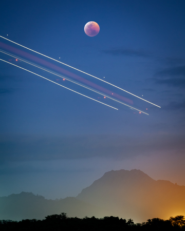 A rare photograph of the January 2019 super blood wolf moon lunar eclipse rising over Oahu, Hawaii with light trails from an airplane above a mountain landscape.
