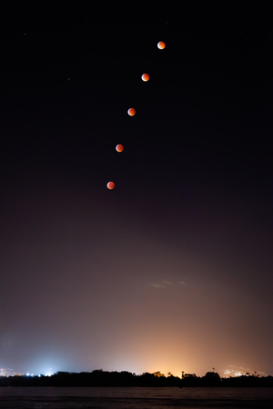 Composite photo of January 2019 super blood wolf moon lunar eclipse rising over Pearl Harbor, Oahu, Hawaii, USA.. 스톡 콘텐츠
