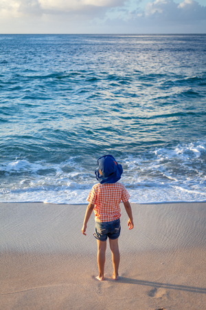 Young boy in colorful clothes staring into the ocean surf on a sandy beach in Hawaii.