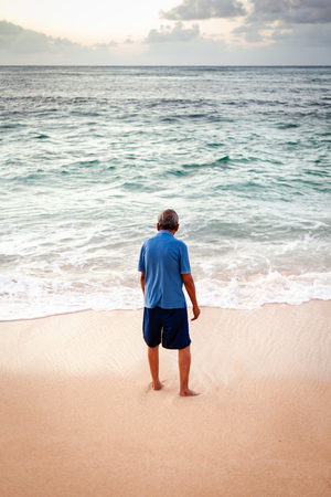 Old man in colorful clothes staring into the ocean surf on a sandy beach in Hawaii.