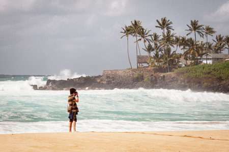 Young man on north shore beach of Oahu, Hawaii taking travel landscape pictures. 스톡 콘텐츠