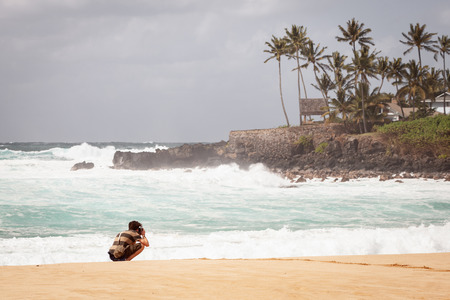 Young man on north shore beach of Oahu, Hawaii taking travel landscape pictures. 스톡 콘텐츠 - 122470344