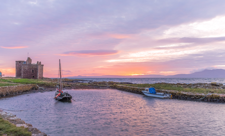 An evening image taken in December of last year 2016 as the sun was going doing behind Arran. There is soft reflected red light on the castle walls and on the water. Editorial