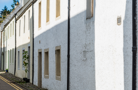 Scottish Typical Terraced Village Houses with a single green plant type tyree outside one of the doors. A typical row of terraced houses often seen in Scotlands villages.i7 Stockfoto