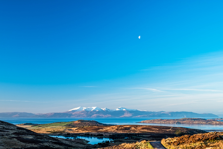 The Arran Hills early mornoing in winter snow capped and a small moon above in the sky