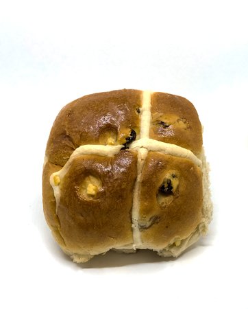 A slightly squashed but home made delicious hot cross bun in time for Easter. Room for text. Stockfoto