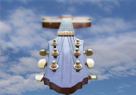 Looking down an accoustic guitar head and neck to the blue sky . There is space for text on each side of the image which gives the impression that the guitar is floating in the sky. Retro type image from the 80s