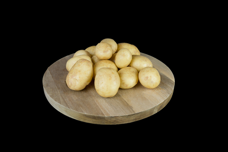 A pyramid of New Ayrshire Potatoes straight out of the contributers garden and cleaned and stacked on a wooden board which is then isolated on a black background. Stock fotó
