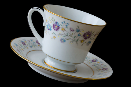 Teacup and Saucer with a floral print on both the cup and the saucer. Image taken close and is displayed at an angle in natural light. Family heirloom owned by the contributor. Origins unknown. Image has a dutch tilt to add effect. Stok Fotoğraf