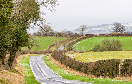 Icy Road with lightly covered snowie hills in the far distance. The Trees are stripped of leaves due to the harsh Scottish Winter and the hedge rows are devoid of foliage. Stock Photo