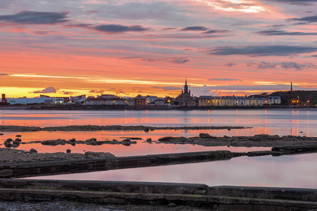 A beautiful  sunset over Ardrossan and Arran with the firey sun reflecting off the water on the bay between Saltcoats and Ardrtossan. Redactioneel