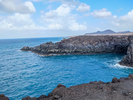 The eroded volcanic sea caves and cliffs at Los Hervideros in Lanzarote Spain where people make their way through narrow passageways to view the caves. Stock Photo