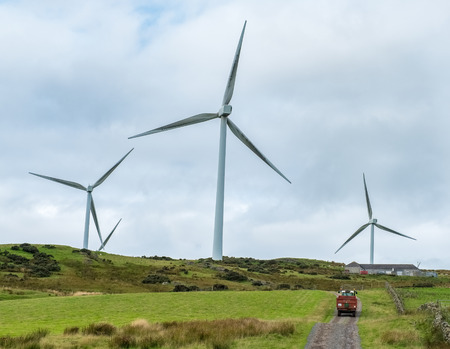 Massive windturbines above Ardrossan in North Ayrshire Scotland. Farm vehicle in the image indicates scale.
