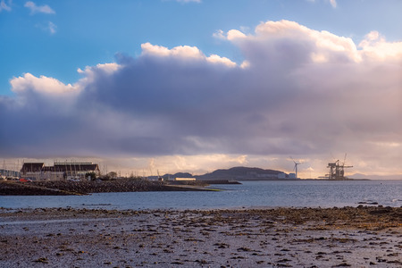 Largs Foreshore looking into the marina across a small bay at low tide with the cranes and wind turbine of Hunterston in the far hazy distance. Zdjęcie Seryjne