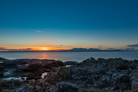 The Isle of Arran from Portencross rocky shore line as the sun goes down on a cold Christmas Eve in Scotland. Stock Photo