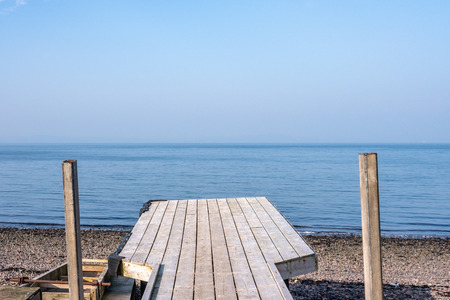 A rickety old Slanted wooden jetty and the beautiful blue sea and sky in Largs on the west coast of Scotland.