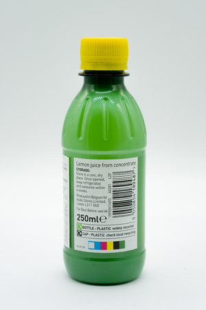 Largs, Scotland, UK - February 04, 2019: An Asda branded bottle of lemon juice in a recyclable plastic bottle and cap. Label has all relevant recycling and safety symbolsinline with current UK recycling initiatives .