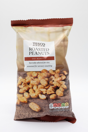 Largs, Scotland, UK - February 19, 2019: Tesco Branded Roasted Peanuts in recyclable plastic bag with nutritional and recycling information on back.