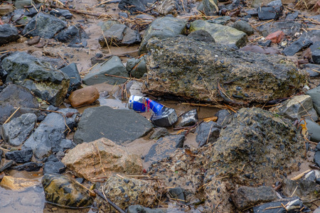 Irvine, Scotland, UK - March 18, 2019: Environmental image of Waste with Aluminium Red Bull Drinks Can being discarded on the beach in Irvine  Scotland.