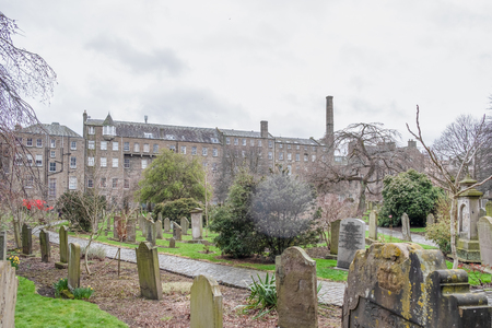 Dundee, Scotland, UK - March 22, 2019: Looking through the Old Howff Graveyard to Dundees industrial Past.