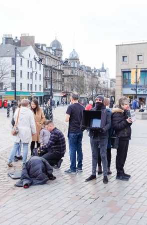 Dundee, Scotland, UK - March 23, 2019: Some people protest with partial facial coverings e.g Plastic tape and head scarfs over mouths holding 'Watch Dominion' placard in Reform Street in the city centre of Dundee in Scotland.