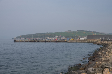 The town of Largs set on the Firth of Clyde on the West Coast of Scotland and looking along the Promenade of the town centre and Largs Pier. Banco de Imagens