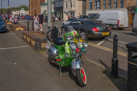 Largs, Scotland, UK - April 20, 2019: The town of Largs set on the Firth of Clyde on the West Coast of Scotland with a gathering of Motor Bikers in the seafront carpark and in particular this particular lime green vespa scooter. 新聞圖片