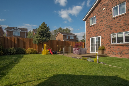 Landscaped garden with grass, new borders planted, a new decking patio and garden ornaments surrounded by new erected wooden fencing all to a modern design. A good image for a landscape gardener designer or garden retail centre