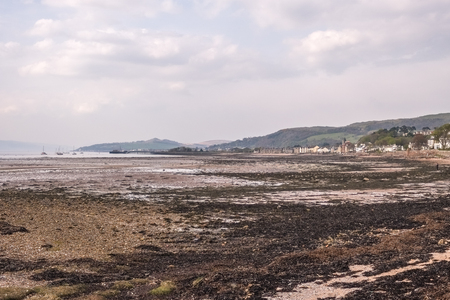 Fairlie Foreshore looking over to Fairlie and Largs and at low tide with lots of seaweed and shingle on the shoreline..