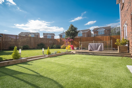 Landscaped garden with grass, new borders planted, a new decking patio and garden ornaments surrounded by new erected wooden fencing all to a modern design. A good image for a landscape gardener designer or garden retail centre Banco de Imagens