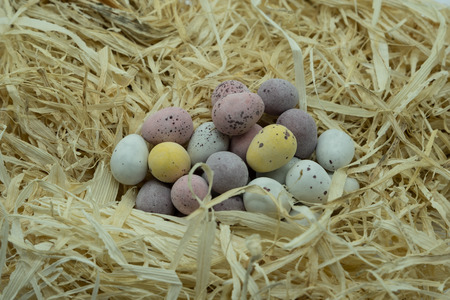 A pile of colourful chocolate eggs on a bed of fresh straw ready for Easter