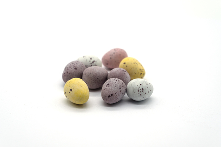 A pile of colourful chocolate eggs on a white background the front egg in focus and the rest softens through the image