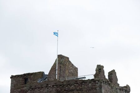 The Scottish Saltire Flag Flying Proudly on top of one of Scotlands castles Ruins on a windy day. Stock Photo