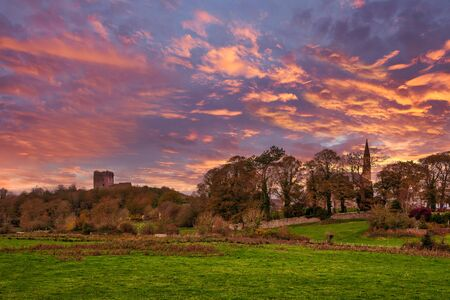 The ancient and almost derelict ruins of Dundonald castle that sits proudly above the town of Dundonald in South Ayrshire Scotland. All at the end of the day with a blazing red sunset sky.